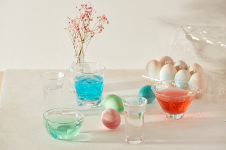 Easter eggs dyeing in glass with colors 版權商用圖片