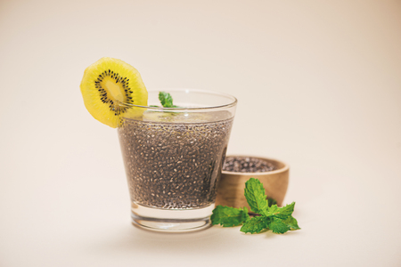 Selective focus of chia seeds drink with water in transparent glass with slice of kiwi Stock Photo