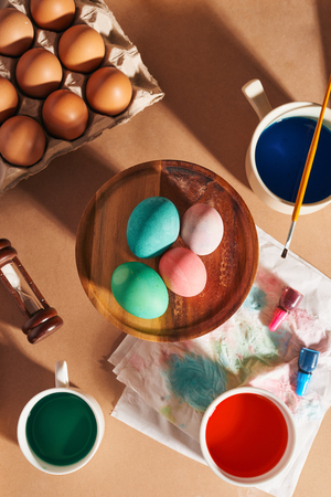 Eggs, colorful paints, brushes, pencils on a wooden background, coloring eggs, preparing for Easter, spring seasonal holiday
