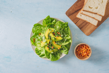 Healthy green salad from avocado, cucumber, grapes, parsley and lettuce with olive oil dressing, balsamic vinegar and grain mustard.