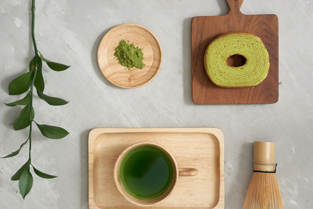 Green tea matcha in a wooden cup with German cake on the brown mat close-up Stock Photo