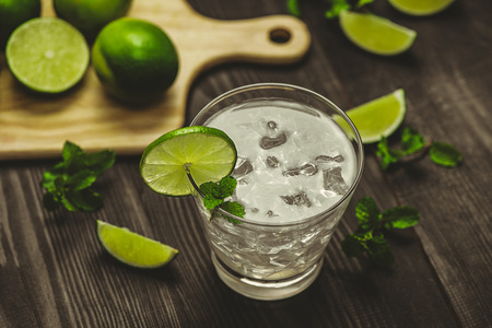 Glass of water with lime, ice and mint. Isolated on wooden background. Stock Photo