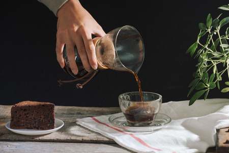 Man pouring cold brew coffee into glass on table