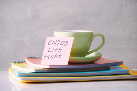 Grüne Tasse mit Aufkleber und Notizbüchern auf der Tischplatte.