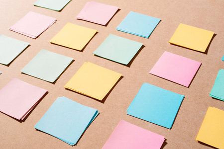Multi colored notepads laying on a wooden plank board surface with copy space