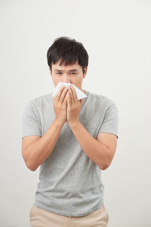 mężczyzna jest chory i kicha na białym tle, azjata