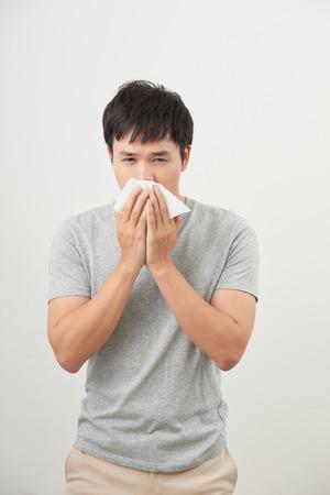 Mann ist krank und niest mit weißem Hintergrund, asiatisch
