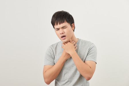 Young Asian man having sore throat  throat related diseases