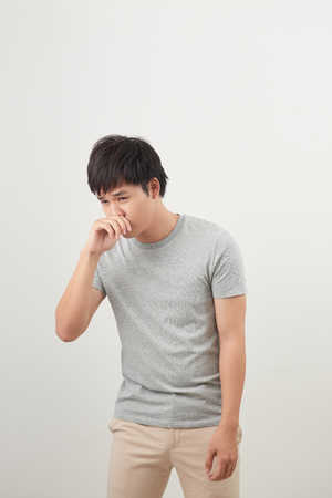 sick man with runny nose portrait; sick asian man with runny nose, cold, flu, illness, contagious disease, health care concept; young adult asian man model Stock Photo
