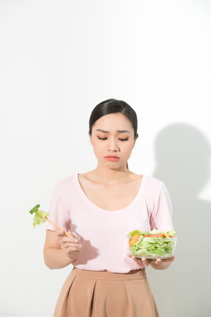 unhappy asian women is on dieting time. girl do not want to eat vegetables and dislike taste of vegetable. 免版税图像 - 122838962