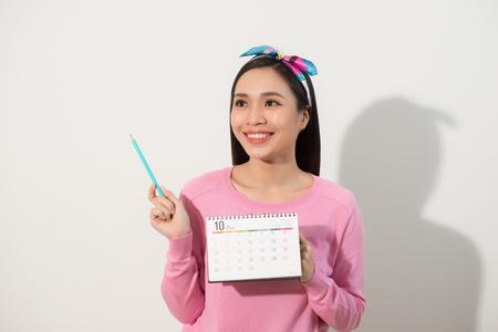 Portret szczęśliwej słodkiej dziewczyny trzymającej swój kalendarz okresów długopisem i odwracającej wzrok na miejsce na kopię na białym tle nad białym tłem Zdjęcie Seryjne