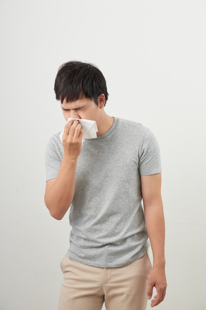 man is sick and sneezing with white background, asian