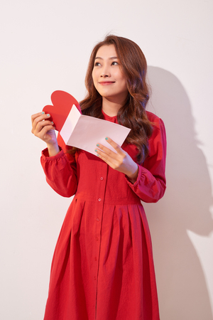 Happy female enjoying greeting card, reading with pleasure love letter, celebrate Valentine day at home Stockfoto