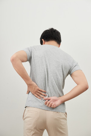 Man with back pain isolated on white background 写真素材