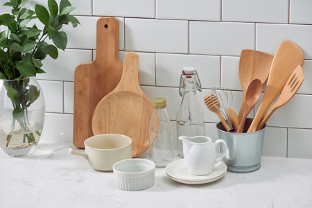 Simple rustic kitchenware against white wooden wall: rough ceramic pot with wooden cooking utensil set, stacks of ceramic bowls, jug and wooden trays.