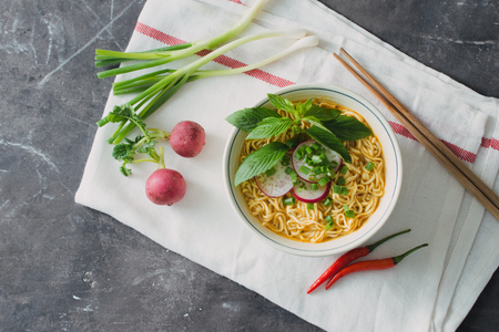 Instant noodles in bowl with radish, herbs and onion Reklamní fotografie - 119469080