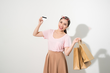 Portrait of a surprised happy girl holding shopping bags and showing credit card while looking at camera isolated over white background Stock Photo