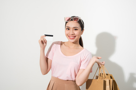 Young beautiful woman with credit card in hand and holding shopping bags over white background Stock Photo