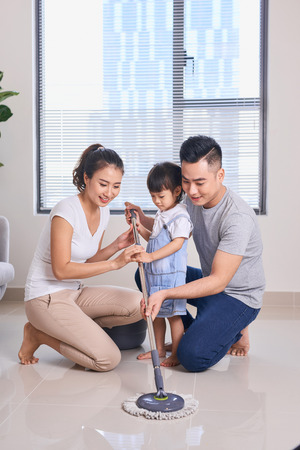 Ordinary family of three doing house cleaning with cleaning equipment 写真素材