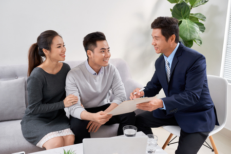 Sales Consultant showing new investment plans to young asian couple 스톡 콘텐츠