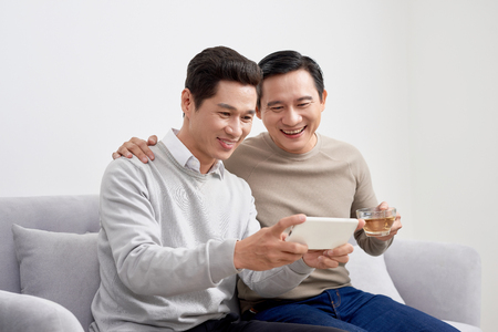 Cheerful young men dressed in casual wear smiling at camera while making selfie photo on front camera