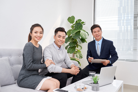 Successful lawyer giving consultation to family couple about buying house 스톡 콘텐츠