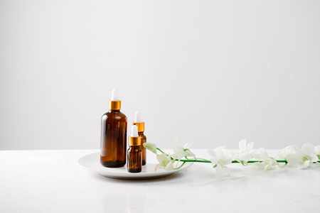 Dropper bottle of organic orchid pure oil on a white surface with orchid heads in the background. Reklamní fotografie