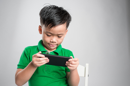 Portrait of an amused cute little kid playing games on smartphone isolated over gray background