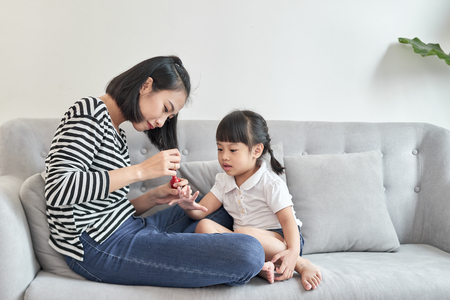 Beautiful young mother is painting the nail varnish to her cute little daughter Stock Photo