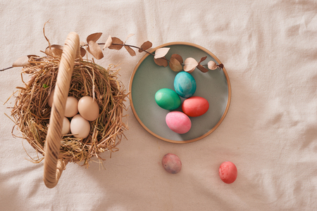 Easter eggs in the nest on rustic linen background Stock Photo