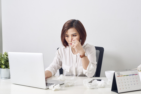 Sad exhausted woman with tissue suffering from cold while working with laptop at table Archivio Fotografico - 120514523