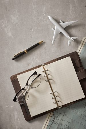 Empty white space in notebook where you can place your text or advertisement. Airplane, magnifying glasses and glasses on the map. Romantic travel