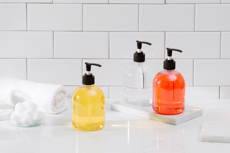 Cosmetic bottles with shower gel, body lotion or shampoo and bath towels. Bathroom accessories. 免版税图像