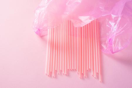 Primo piano di rifiuti di plastica colorati in un sacchetto della spazzatura rosa come posate riciclabili monouso inquinamento spazzatura concetto isolato su sfondo rosa