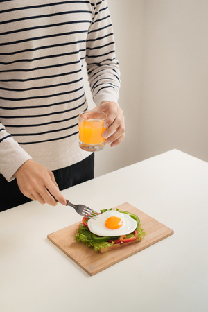 Hands of man cut the eggs on cutting board, served with bread, herbs, sausage and fresh juice. Stock Photo