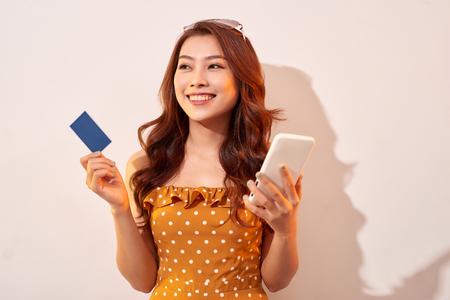 Retrato de una niña feliz sosteniendo un teléfono móvil y una tarjeta de crédito aisladas sobre fondo de biege