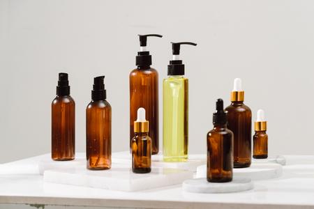 Spa-Kosmetik in braunen Glasflaschen auf grauem Betontisch. Kopieren Sie Platz für Text. Beauty-Blogger, Salontherapie, Branding-Mockup, Minimalismus-Konzept Standard-Bild