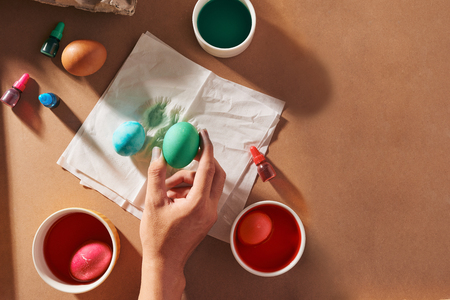 Holidays, tradition and people concept - close up of man hands coloring easter eggs with brush