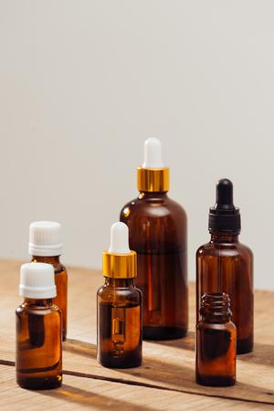 Bottiglie di oli essenziali sulla scrivania in legno con accanto a lume di candela. Set benessere termale.