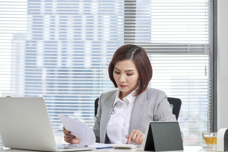 Financial advisor using calculator review financial statement on desk. Accounting concept. 스톡 콘텐츠