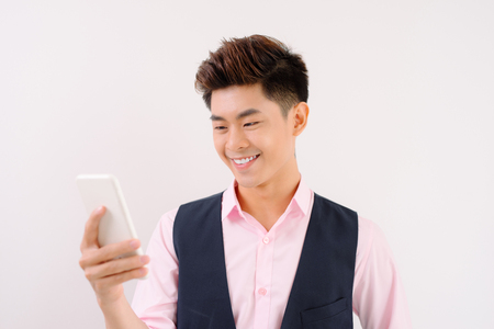 Young cheerful brunete lawyer is standing on the pure light blue background and smiling, reading good news on internet at his mobile phone