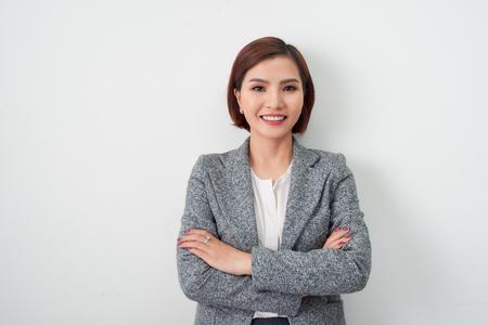 Joven empresaria asiática, brazos de mujer de negocios cruzados sobre fondo blanco.