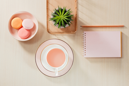 Styled stock photography beige office desk table with blank notebook, macaroon, supplies and coffee cup 写真素材