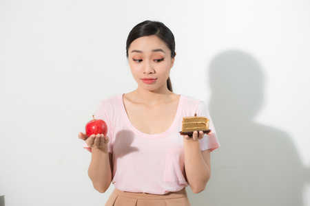 Woman holds in hand cake sweet and apple fruit choosing, trying to resist temptation, make the right dietary choice. Weight loss diet dilemma gluttony concept.