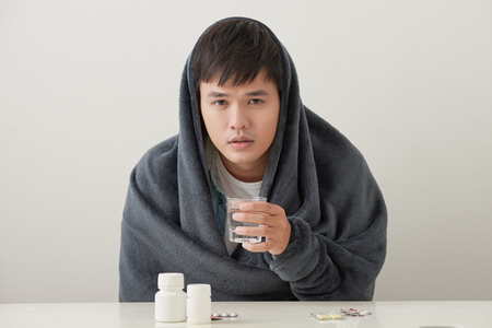 a man wrapped in a warm blanket basks on a light background Stock Photo