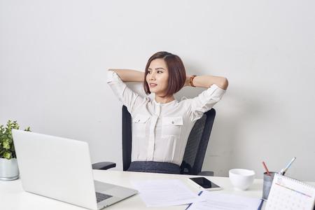 Geschäftsfrau, die sich nach einem Arbeitstag im Büro ausruht und sich die Hände hinter dem Kopf zurücklehnt