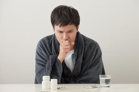 Hombre enfermo acostado en la cama y tosiendo mucho Foto de archivo