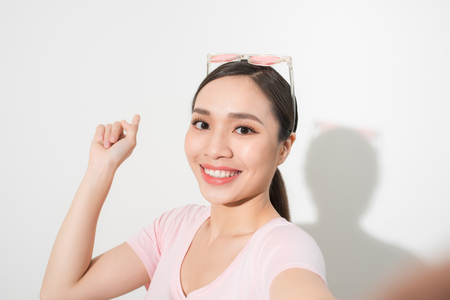 Young happy smile girl take selfie on white background