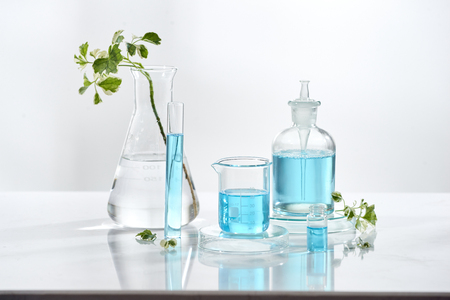 laboratory glass equipment with natural ingredients on white background