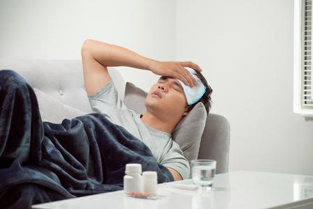 kranker verschwendeter Mann, der im Sofa liegt, das unter Erkältung und Wintergrippevirus leidet, das Medizin-Tabletten im Gesundheitskonzept sieht, das Temperatur auf Thermometer schaut